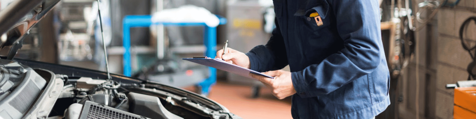 Image of a mechanic in a blue jacket, writing on a clip board while looking at a car's engine.